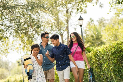 A family walks along the walking paths from the hotel to the theme parks.