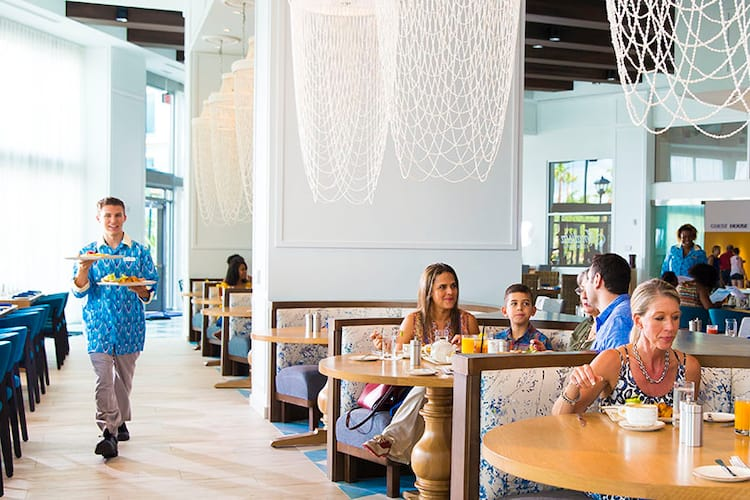 Guests seated at elegant booths eat inside Amatista Cookhouse, the main restaurant at Loews Sapphire Falls in Universal Orlando Resort.