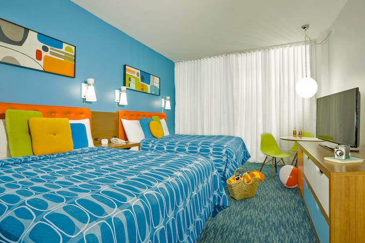The interior of a guest room at Universal Orlando's Cabana Bay Beach Resort, featuring two colorful beds, a flat panel TV, and a table area.