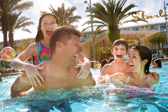 A mother and father hold their children on their backs in the swimming pool at Cabana Bay Beach Resort, a Prime Value on site resort hotel at Universal Orlando.