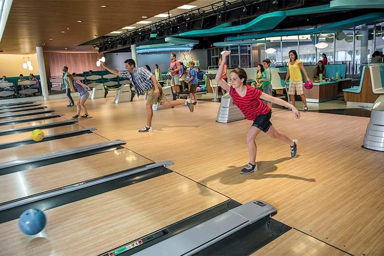 A girl throws a bowling ball down the lane at Galaxy Bowl, a fun, retro bowling alley at Universal Orlando's Cabana Bay Beach Resort.