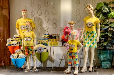A window display shows a mannequin family with Minion themed merchandise at the Universal Orlando Resort Store inside Cabana Bay Beach Resort.