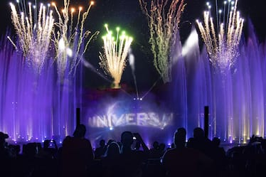 Fireworks and purple-lit water shoot toward the sky over a projection of the Universal globe during Universal Orlando's Cinematic Celebration show.