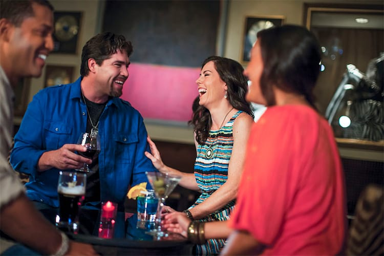 A group of adults sit around a table laughing and smiling while enjoying drinks at Velvet Bar in Hard Rock Hotel, a Premier on site resort hotel at Universal Orlando Resort.