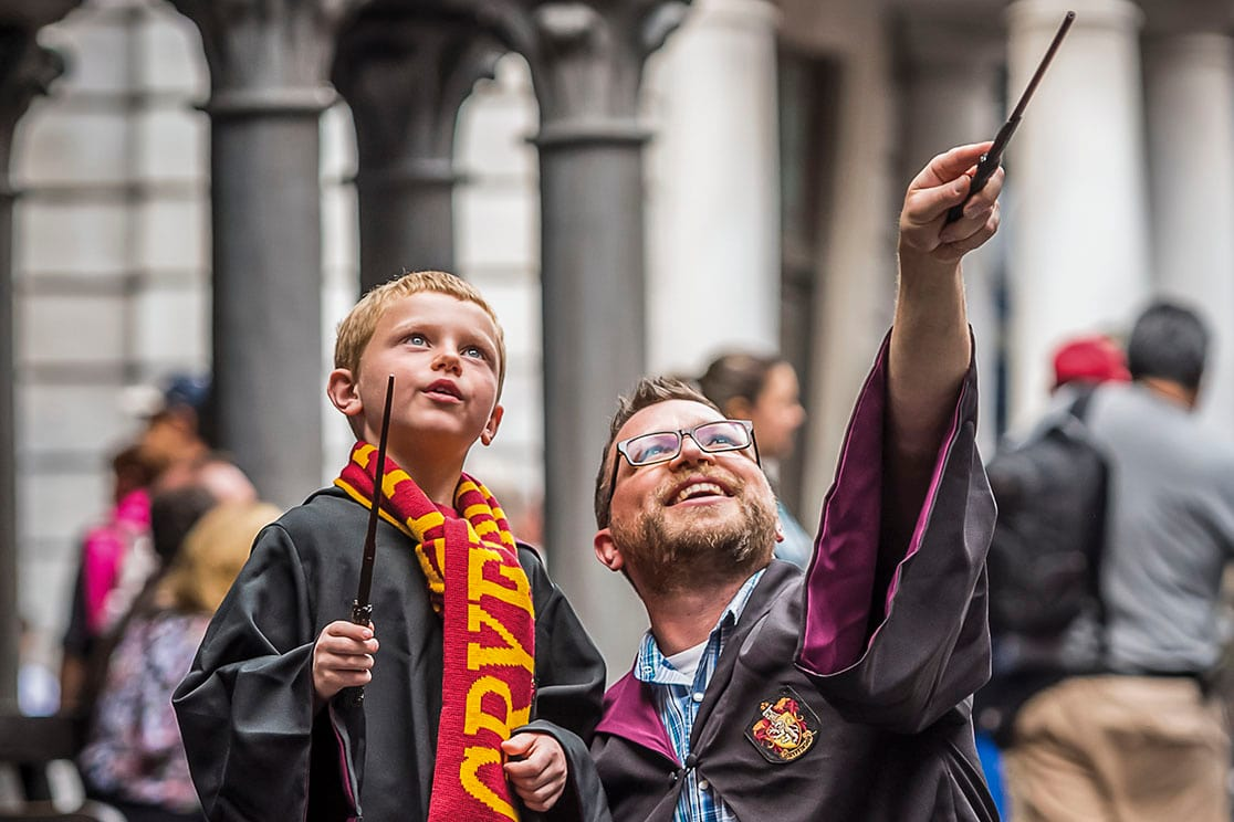 A boy wears a Gryffindor scarf as he and his father hold wands and look upward inside Diagon Alley at Universal Orlando.