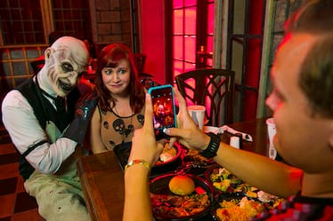 A woman smiles hesitantly as she poses for a photo with a masked man during the Scareactor Dining Experience.