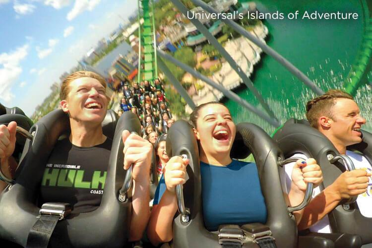 Four young adults scream and laugh while riding in the front row of The Incredible Hulk Coaster at Universal's Islands of Adventure in Orlando.
