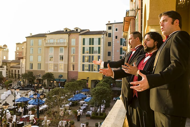 Three men in suits belt out operatic melodies from a balcony overlooking the Piazza at Loews Portofino Bay Hotel in Universal Orlando.