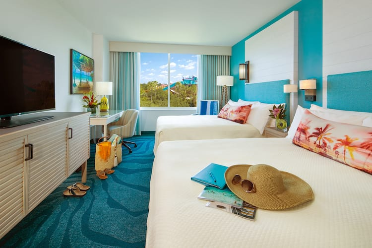 A sunhat and sunglasses sit atop a bed in a stylish white and aqua colored guest room at Loews Sapphire Falls Resort at Universal Orlando featuring two queen beds, a desk and a flat panel TV.