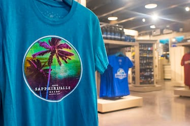 A close-up of a Loews Sapphire Falls Resort T-Shirt with the Universal Studios Store in the background.