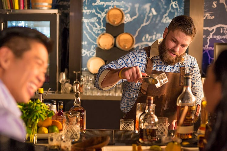 A bartender smiles as he prepares a drink at Strong Water Tavern, a dining location at Universal Orlando's on site hotel, Loews Sapphire Falls Resort.