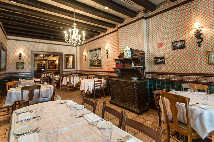 Dining tables with white tablecloths within a charming wallpapered room at Mama Della's restaurant.
