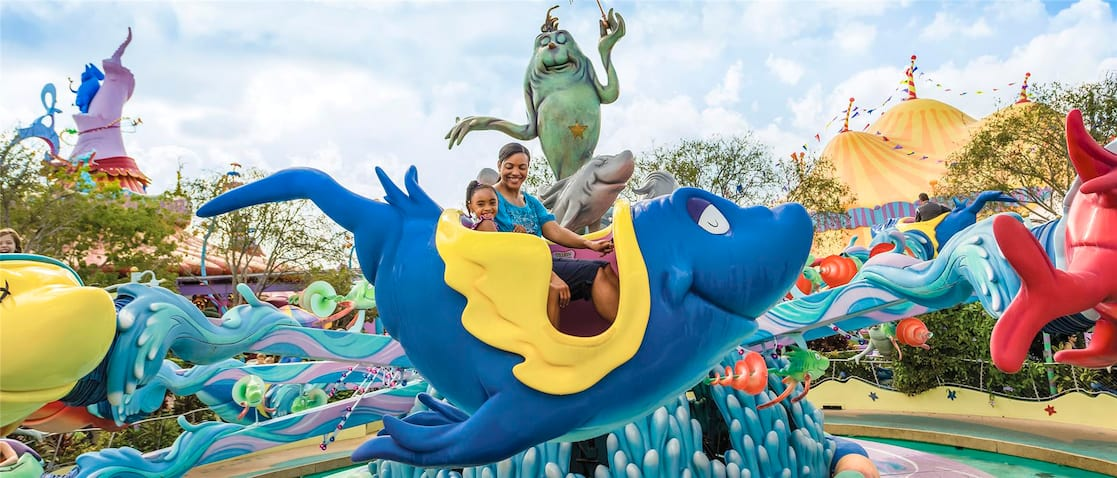 A mother and daughter ride inside a fish car on One Fish, Two Fish, Red Fish, Blue Fish at Seuss Landing in Universal's Islands of Adventure.