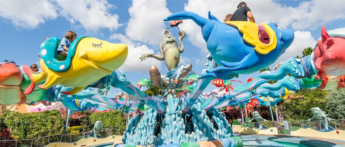 Flying fish vehicles soar above the ground and circle a squirting fountain on One Fish, Two Fish, Red Fish, Blue Fish at Seuss Landing in Universal's Islands of Adventure.