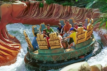 A large raft full of people barrels down the whitewater rapids of Popeye and Bluto's Bilge Rat Barges in the Toon Lagoon area of Universal's Islands of Adventure Orlando.