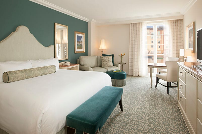 The interior of a King Guest Bedroom in Loews Portofino Bay Hotel at Universal Orlando, complete with white linens, royal turquoise accents, and lush furniture and decor.