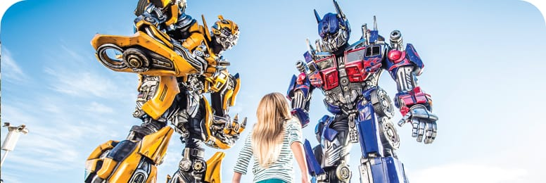 Girl staring up at transformers.