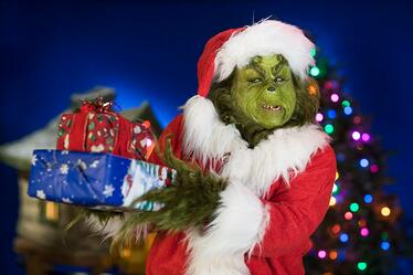 The Grinch gives a sly look while holding Christmas presents and standing in front of a colorful Christmas tree at Universal Orlando's Grinchmas Who Liday Spectacular.