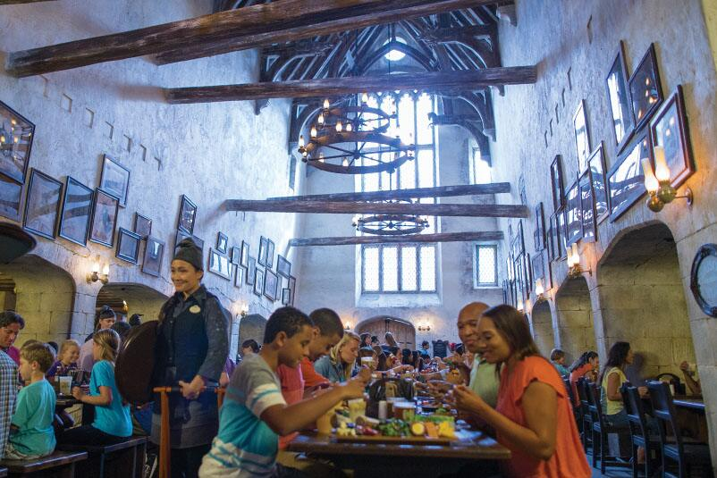 People enjoying traditional British food in the Leaky Cauldron restaurant in The Wizarding World of Harry Potter Diagon Alley at Universal Studios Orlando.