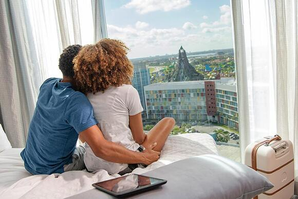 A couple looks out their Universal Orlando hotel window at the Volcano Bay.