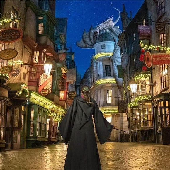A girl wearing a wizard robe stands in Diagon Alley, decorated for the holidays at night time.
