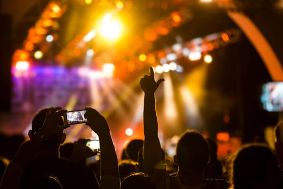 Concert guests enjoy a live performance and several people record it with their phones.
