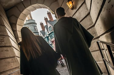 A couple wearing wizard robes walks hand in hand towards Diagon Alley inside Universal Orlando Studios Orlando.