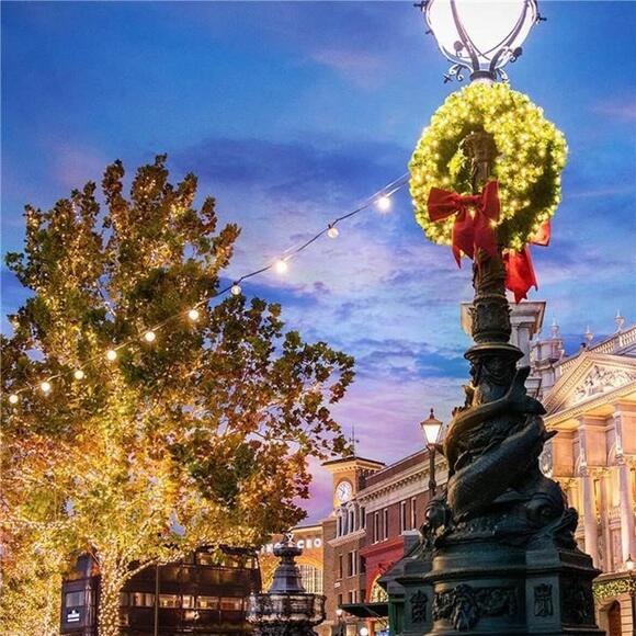 The London area of Universal Studios Florida is decorated with wreaths and holiday lighting at dusk.