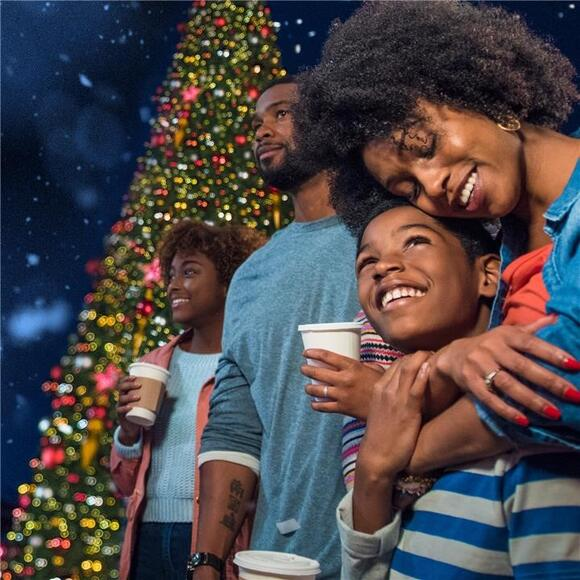 A family enjoys their hot beverages as they take in the Holiday Sights at Universal Studios Orlando.