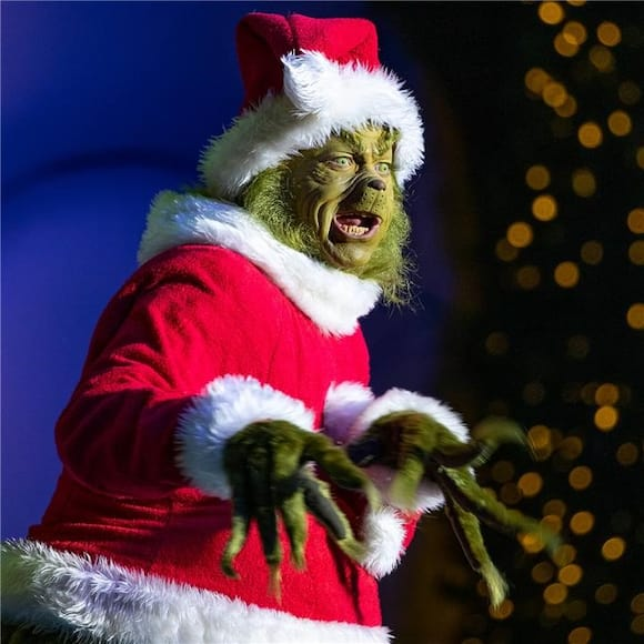 The Grinch wears a Santa costume during the Holidays at Universal Orlando Resort.