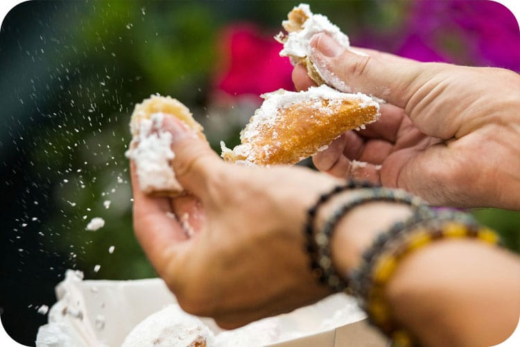 A guest enjoys a beignet at Mardi Gras.