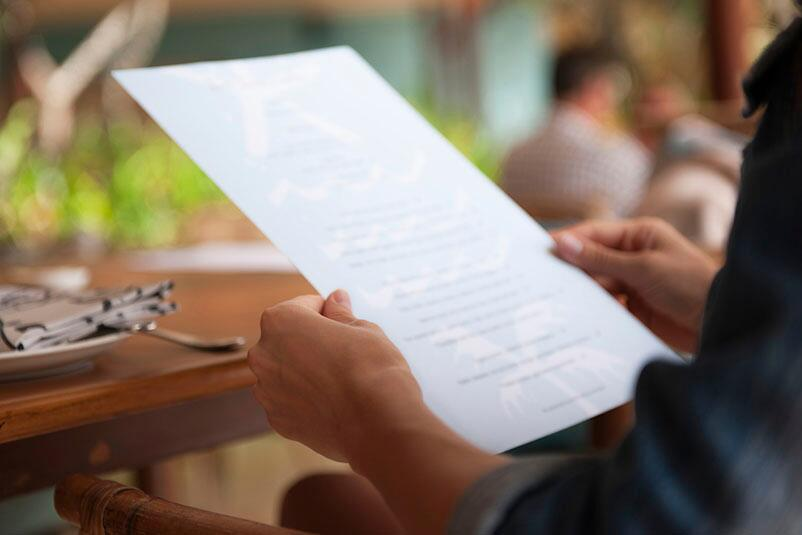A Restaurant Guest Holds Menu While Sitting At Table