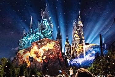 In an artist conceptual rendering, Hogwarts castle is lit up at night with colorful projections depicting the Hogwarts houses.