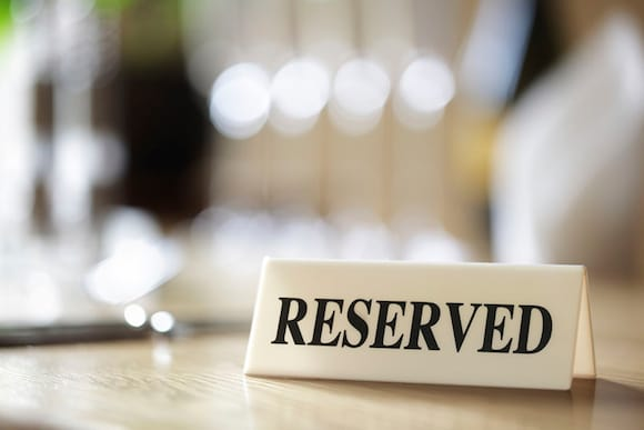 A white sign with black lettering that reads 'RESERVED' sits on a tabletop.