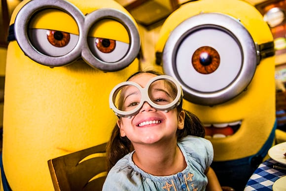 A little girl smiles alongside two Minions at the Superstar Character Breakfast at Universal Orlando Resort.