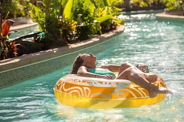 Picture of girl in bathing suit relaxing on inflatable tube as she floats down winding river.