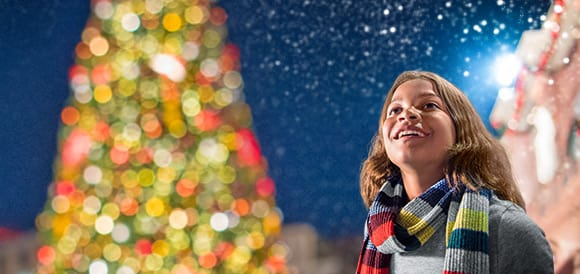 Girl smiling in front of Christmas Tree.