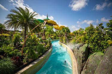 The Teawa Fearless River at Universal's Volcano Bay water theme park flows quickly and is lined with tropical landscaping.