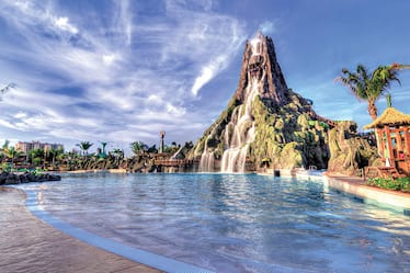 A picturesque view of a lagoon and water rushing down the volcano at Universal's Volcano Bay water theme park.
