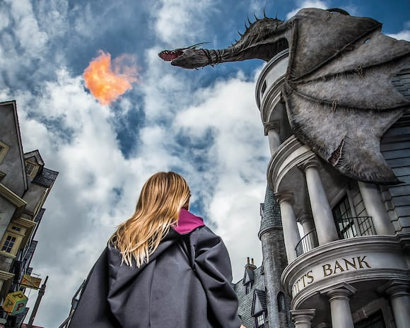 A girl looks up as the dragon perched atop Gringotts blows fire above Diagon Alley in Universal Studios Florida.