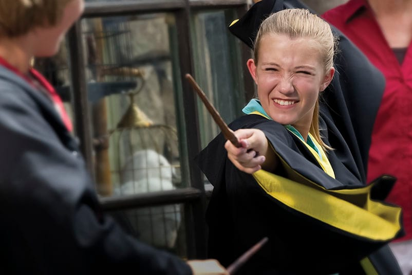 A little girl wearing Hufflepuff robes waves her wand as she casts a spell in The Wizarding World of Harry Potter Diagon Alley at Universal Studios Florida.