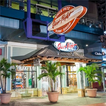 The outside of Quiet Flight surf shop at Universal CityWalk features an awning and potted palm trees for a coastal look.